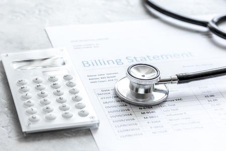 医療費請求のステートメント、聴診器、石のテーブル上の電卓