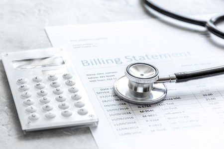 Health care costs with billing statement, stethoscope and calculator on stone table