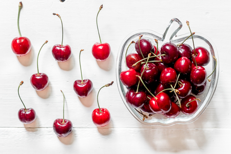 A lot of cherry in bowl on white background top view