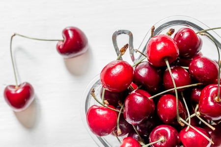 A lot of cherry in bowl on white background.