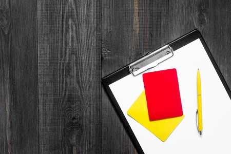 Yellow and red referee cards on wooden background top view copyspace