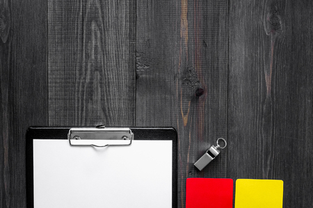 Yellow and red referee cards and whistle on wooden background top view copyspace