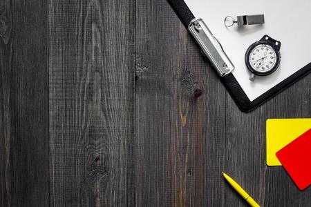 Scheidsrechter tools. Gele en rode scheidsrechterkaarten, fluitje, chronometer, stootkussen, pen op houten hoogste mening als achtergrond copyspace Stockfoto
