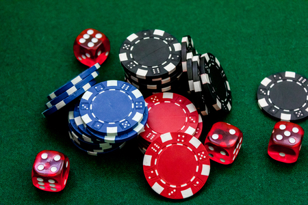 bets: Poker chips and dice on a green gaming table top view. Stock Photo