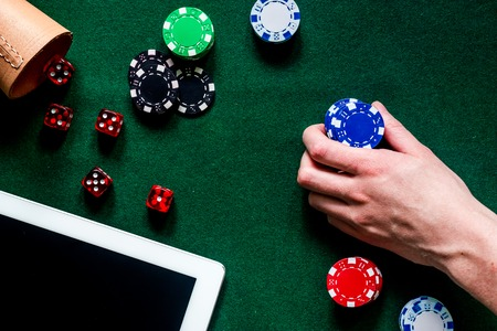 Compulsive gambling. Hand with poker chip and the dice nearby keyboard on green table top view copyspace Stock Photo
