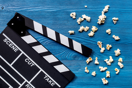 Watching the film. Movie clapperboard and popcorn on wooden table background top view. Stock Photo