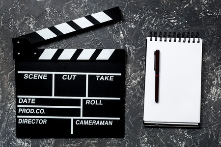 screenwriter: Work table of producer. Movie clapperboard and notebook on grey stone background top view Stock Photo