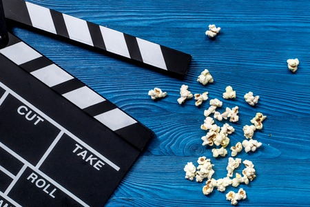 Watching the film. Movie clapperboard and popcorn on blue wooden table background top view