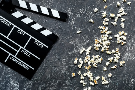 Watching the film. Movie clapperboard and popcorn on grey stone table background top view. Stock Photo