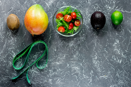 Healthy diet. Salad with fresh products and fruits mango, mangosteen, kiwi and measuring tape on stone table top view copyspace