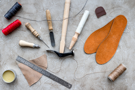Set of cobbler tools on grey stone desk background top view. Stock Photo