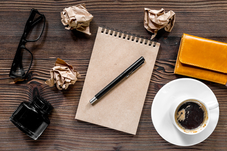 Writer workplace with vintage notebook, pen, glasses and coffee on wooden table background top view.