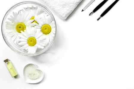 natural cosmetics design with chamomiles for manicure on white table background top view space for text.