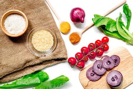 白いキッチン デスク背景トップ ビューに野菜や米のパエリア