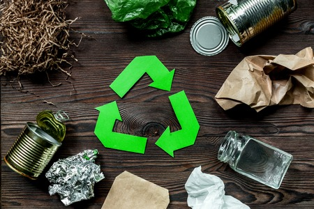 Eco concept with recycling symbol on wooden table background top view. Stock Photo