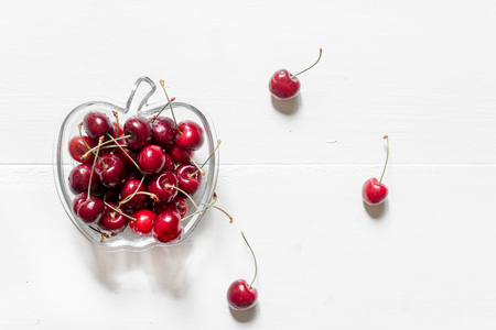 A lot of cherry in bowl on white background top view. Stock Photo