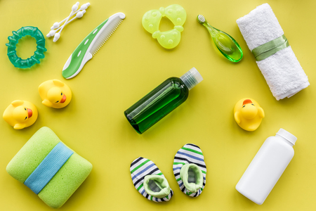 Cosmetics for baby bath taking, towel and toys on yellow background top view pattern