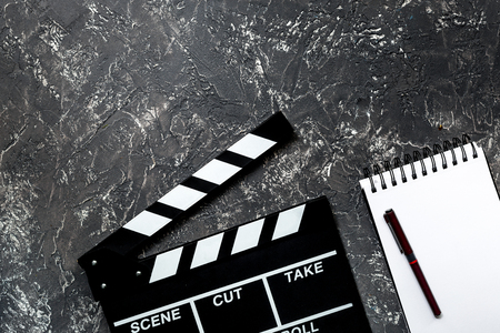 screenwriter: Work table of producer. Movie clapperboard and notebook on grey stone background top view copyspace.