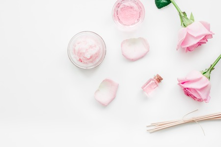 Cosmetic set with rose blossom and body cream for treatment on white desk background top view mock-up Stock Photo