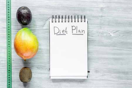 Slimming. Notebook for diet plan, fruits and measuring tape on grey wooden table top view mock up. Stock Photo