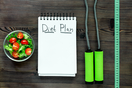 heathy: Heathy food for slimming. Notebook for diet plan, salad and measuring tape on wooden table top view mock up.