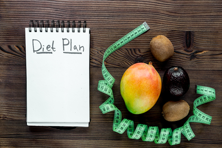 Slimming concept. Notebook for diet plan, fruits and measuring tape on wooden table top view mock up.