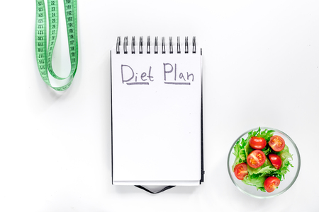 Notebook for diet plan, salad with fresh products and measuring tape on white background top view.