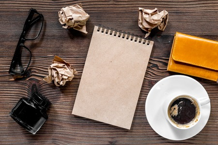 Writer workplace with vintage notebook, pen, glasses and coffee on wooden table background top view mockup