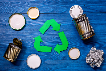 Paper recycle sign with steel garbage on blue table background top view. Stock Photo
