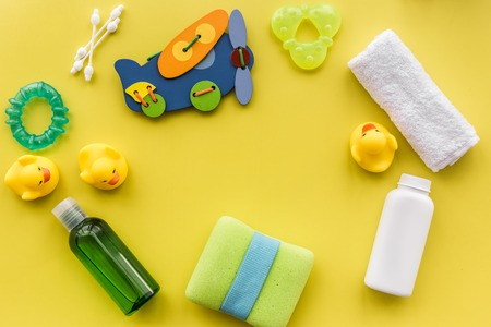 Cosmetics for baby bath taking, towel and toys on yellow background top view space for text