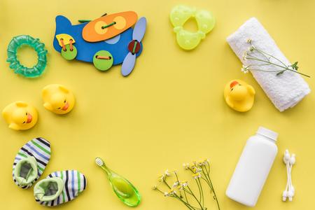 Schoonheidsmiddelen voor babybad het nemen, handdoek en speelgoed op gele achtergrond hoogste meningsruimte voor tekst
