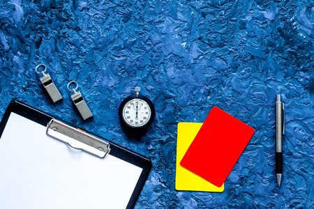 Set to judge competition. Yellow and red cards, stopwatch, whistle, pad, pen on blue table background top view. Stock Photo