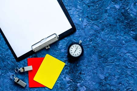 Set to judge competition. Yellow and red cards, stopwatch, whistle, pad on blue table background top view. Stock Photo