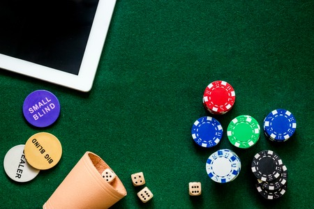 Compulsive gambling. Poker chips and the dice nearby tablet on green table top view.