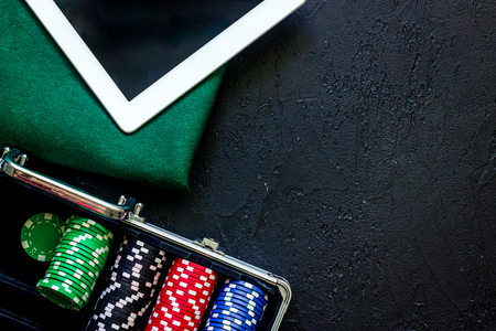 Poker set in a metallic case, green gambling cloth and tablet computer on a grey table top view.