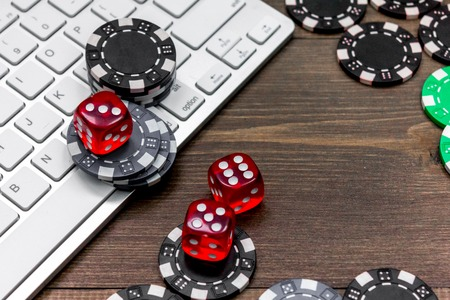 Online poker. Chips and the dice nearby keyboard on wooden table top view. Stock fotó