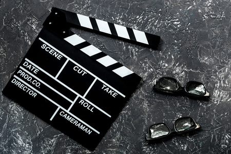 screenwriter: Attributes of film director. Movie clapperboard and sunglasses on grey stone table background top view.