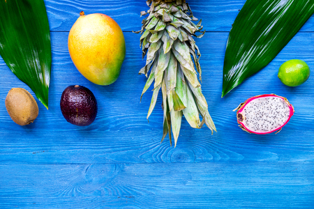 Exotic fruit meal. Dragonfruit, mangosteen, mango, kiwi, lime and pineapple on blue wooden table background top view.
