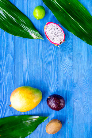 Exotic fruit meal. Dragonfruit, mangosteen, mango, kiwi, lime on blue wooden table background top view.