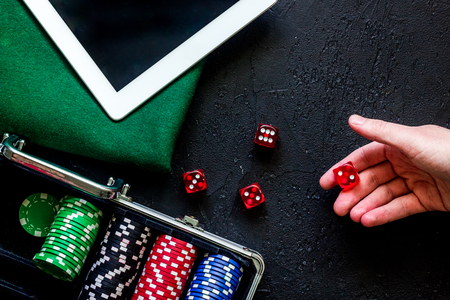 Hand is rolling the dice. Poker set in a metallic case, green gambling cloth and tablet computer on a grey table top view.