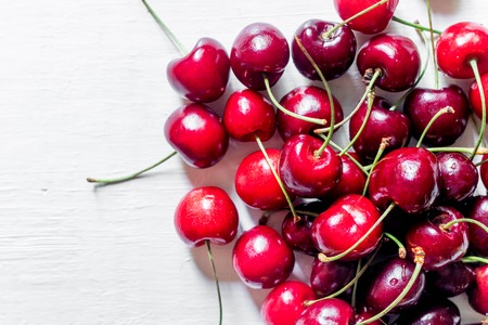 Fruit concept. A lot of cherry on white background top view copyspace.