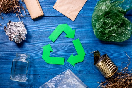 Garbage for recycling with recycling symbol on blue wooden background top view. Stock Photo