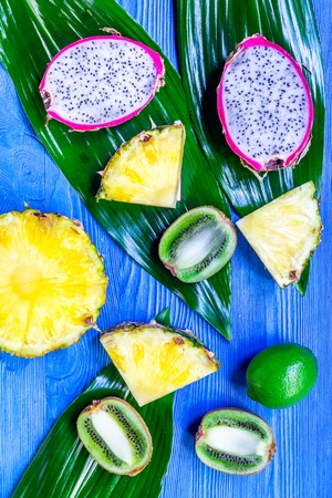Pieces of exotic fruits. Dragonfruit, pineapple and kiwi on blue wooden background top view Stock Photo