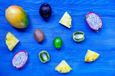 Pieces of thai fruits. Dragonfruit, mangosteen, mango, kiwi and lime on blue wooden background top view copyspace