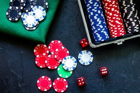 Poker set in a metallic case and green gambling cloth on a grey table top view