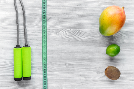 Slimming diet. Fruits mango, lime, kiwi and skipping rope on grey wooden table top view copyspace Stock Photo