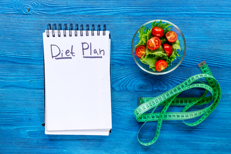 Notebook for diet plan, salad and measuring tape on blue wooden table top view mock up.