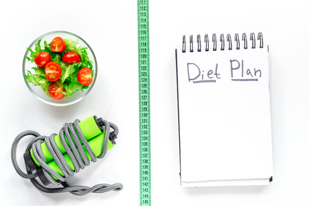Notebook for diet plan, salad with fresh products, jump rope and measuring tape on white background top view. Stock Photo