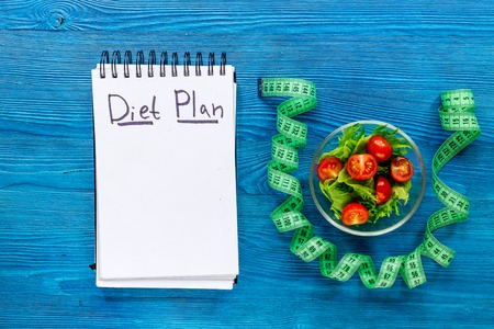 Notebook for diet plan, salad and measuring tape on blue wooden table top view mock up