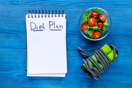 Notebook for diet plan, salad with fresh products and jump rope on blue wooden table top view mock up Stock Photo